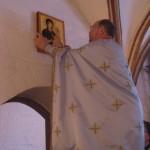 Og anbringer ikonen på dens krog over indgangsdøren til Klosterkirken
